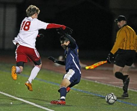 11/14/12 Lynn, MA: Somerville's Ethan Sweeting (left) knocks Needham's Matthew Brand (right) off the ball and out of bounds, first half action. Somerville and Needham met in a boy's high school soccer tournament game at Manning Field. section:spts topic: 15d1soccers (Jim Davis/Globe Staff)