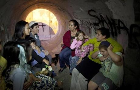 Israelis take cover in a large concrete pipe after a rocket was launched from the Gaza Strip Thursday in Kiryat Malachi.