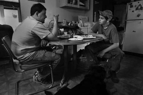 Groveton, N.H., 05-13-11- l-r Sitting in his parent's kitchen, Pete Gilcris (cq) and son Nick (cq) strategize over a french fry lunch. They are under the gun to finish Nick's Camaro for opening day at Riverside Speedway in two days. Pete broke his neck racing in 2010, and Nick rolled his car over 6 times during his first year of racing when he was 12. (Globe staff photo / Bill Greene)