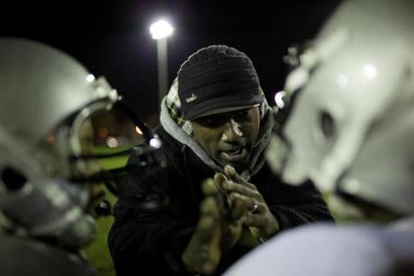 Volunteer coach Rashad Wilson explained an offensive play during the Boston Raiders football practice.
