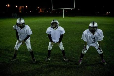 Three members of the Pop Warner football team, the Boston Raiders, lined up in formation during football practice in Dorchester.