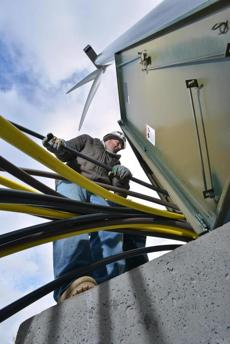 Electricician's apprentice Brian DiCaienzo works with copper cables at the base of a wind turbine being completed at Varian Semiconductor in the Blackburn Industrial park.