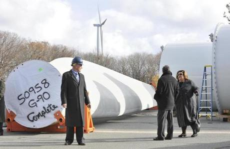Jim Sweeny, president of developer Sustainable New Energy stands beside the base of one of the blades of the wind turbine that will be erected at Gloucester Engineeering in the Blackburn Industrial park as residents arrive for a ceremony to sign one of the blades before it is erecteed.