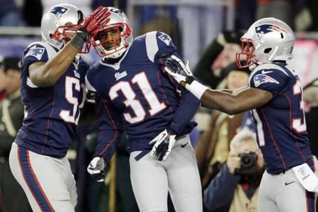 Talib was congratulated by Jerod Mayo, left, and Alfonzo Dennard, right, after his score.