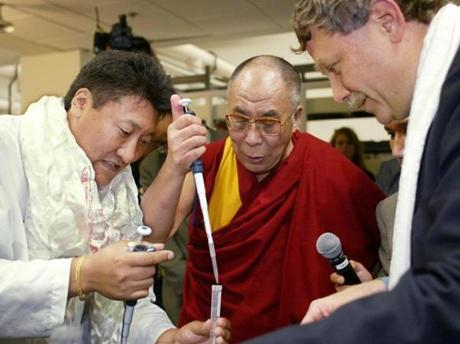 The Dalai Lama, assisted by Yama Chopel (left) and Eric Lander, prepares mouse DNA for sequencing while visiting an MIT research lab.