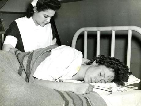 November 29, 1942 / Sophie Urban of Dorchester rested in a hospital emergency ward set up in Boston City Hospital after receiving treatment for burns suffered in flames that swept the Cocoanut Grove night club, trapping scores of people inside. The lipstick