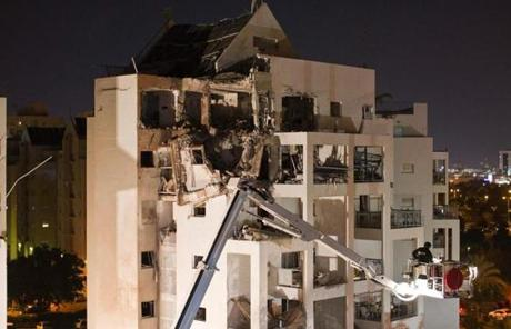 An Israeli worker was lifted by a crane to survey a building damaged by rocket fire in Rishon LeZion.