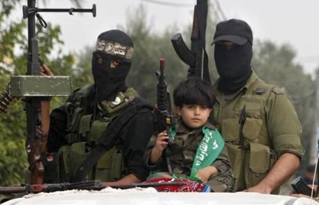 A Palestinian boy and militants of the Izzedine Al-Qassam Brigades, the armed wing of Hamas, attended funerals of five Hamas militants.