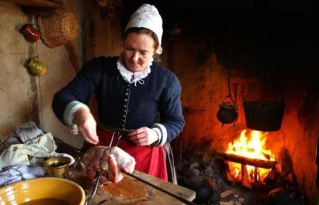 Pilgrim roleplayer Bridget Fuller seasoned pork she will cook in her home fire for two hours.