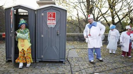 A clown exited a portable toilet prior to the parade.