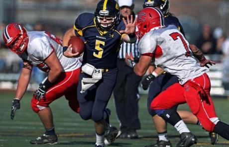 Andover quarterback CJ Scarpa tried to elude Central Catholic's Santino Brancato in the fourth quarter. Andover won, 22-19.