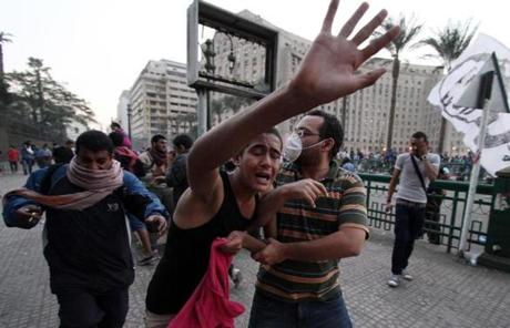 Protesters ran as they suffer from tear gas inhalation fired by Egyptian riot police. Protests broke out around the country after President Mohammad Morsi after granted himself broad powers.