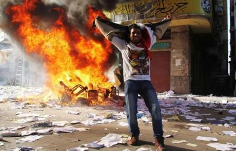 A protester celebrated as items from an office of Morsi's party were burned in the street.