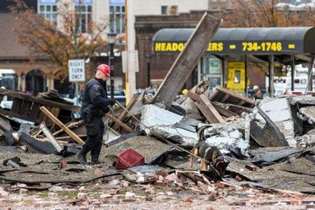 A State Police officer inspected the rubble after a natural gas explosion leveled Scores Gentleman's Club in Springfield.