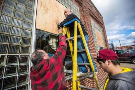 AA Automotive and Repair owner Rene Young (center) boards up some broken windows.