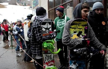 Snowboarders and skiers waited for a ride up Loon Mountain.