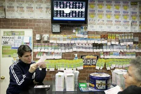Debbie Baker of East Boston looked at Powerball tickets at Lanzilli's Groceria in East Boston on the day before the drawing for the game's biggest jackpot ever.