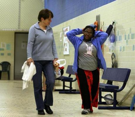 Cathy Tobyne (left) with Ayan Kassim during a mentoring session in the pool at the Hogan Regional Center in Danvers.