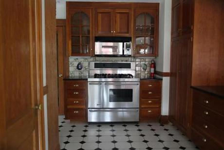 The kitchen has black granite counters, glass fronted cabinets, and stainless steel appliances including a double oven.