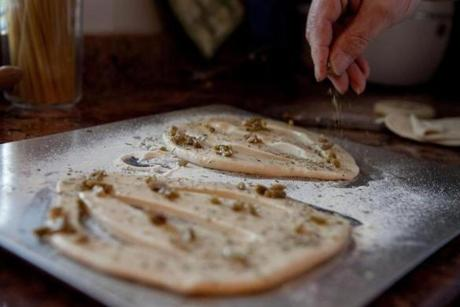 Chef Etienne Jaulin sprinkled herbs and olives onto the dough.