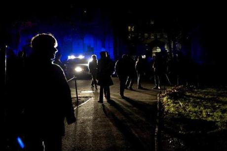 A police car lighted the way as students walked through Harvard Yard during a power outage that plunged much of Cambridge into darkness.