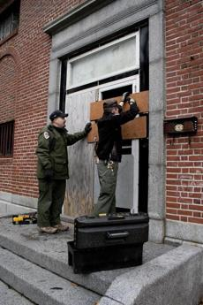 DCR ranger Ray McKinnon (right) puts a temporary band-aid on the door to attempt to secure the property with help from DCR Lieutenant Tom Bender (left).