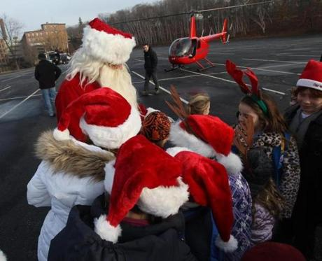 Stow, MA--12/3/12 -- The Maynard parade Santa (doesn't want his name used) gives out candy canes after arriving in Ellie Callahan's helicopter at the staging area of the Maynard holiday parade. (Joanne Rathe/Globe Staff) Topic: 03helicopter Reporter: david filipov