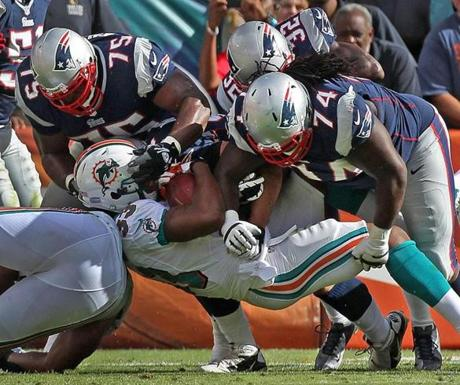 Patriots defenders Vince Wilfork Devin McCourty  and Kyle Love combined to stop Miami running back Daniel Thomas.