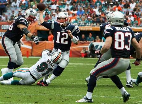 Despite having Dolphins DE Cameron Wake wrapped around his legs, Patriots quarterback Tom Brady spotted an open Wes Welker with a pass that gave New England the ball at the Miami 11 yard line.
