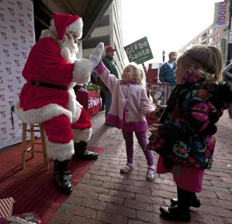 Samantha Walker, 3, greeted Globe Santa outside the Wang Theater in Boston.