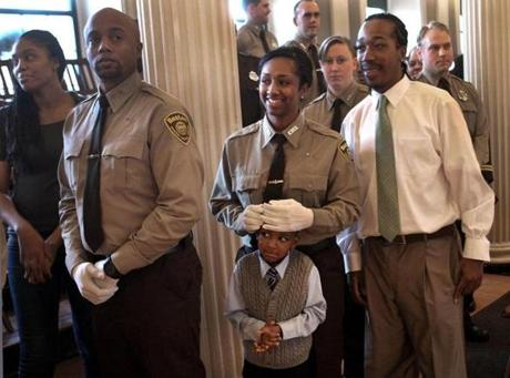 Recruit Taishana Lewis held her 5-year-old son Tyler in line at her graduation ceremony from the Boston EMS Academy. She was inspired to become an EMT by those who responded when her brother, Matthew Lewis-Grant (right) was wounded in a 2009 drive-by shooting. Dec. 3, 2012.