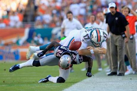 Dolphins quarterback Ryan Tannehill was hit by cornerback Kyle Arrington as Miami head coach Joe Philbin looked on.