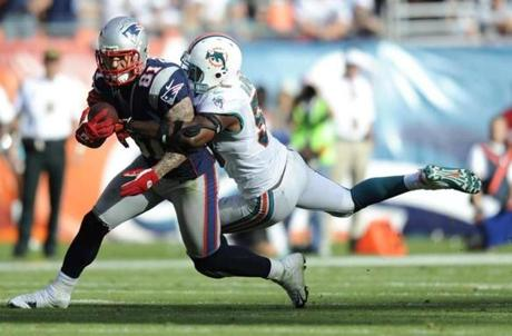 Dolphins linebacker Karlos Dansby grabbed Patriots tight end Aaron Hernandez during the second half.