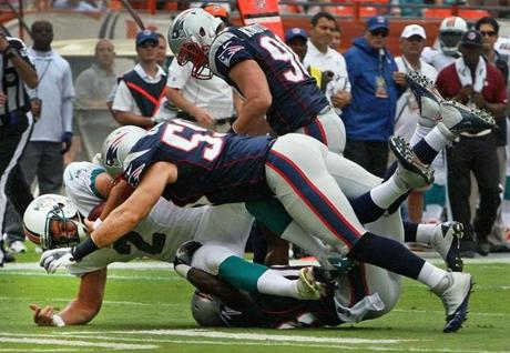 Dolphins punter Brandon Fields was brought down by Patriots defenders after he couldn't handle the snap from center cleanly in the first quarter.