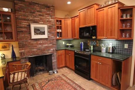 The renovated kitchen has a brick fireplace and cherry cabinets.