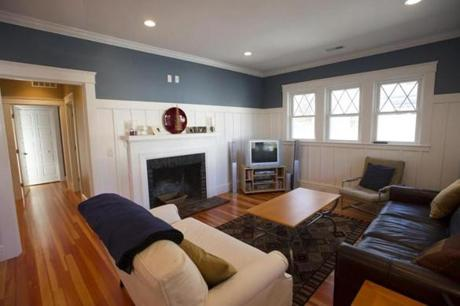 In the fireplaced living room, wainscoting graces the walls.