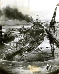 December 7, 1941: In the foreground of the Pearl Harbor drydock was the wreckage of the US Destroyer Downes (left) and USS Cassin. In the rear, relatively undamaged was the USS Pennsylvania, the 33,100 ton flagship of the Pacific Fleet.