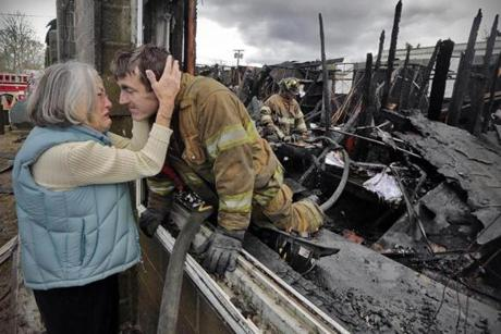 Ruth Nicolaci embraced her son, Fire Lieutenant G. Bourne Knowles, Wednesday after he helped in the fight to save the Fairhaven landscaping business she started with Knowles's father. Officials are working to determing the cause of the fire.