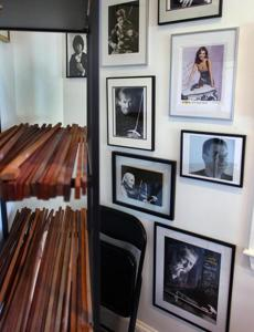 Benoit Rolland's home shop has photos of some of his famous clients. The wood that is used for the bows sits on the shelves.