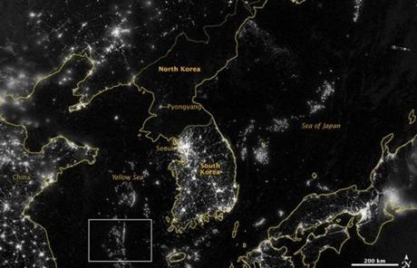 "NASA image acquired September 24, 2012 City lights at night are a fairly reliable indicator of where people live. But this isn't always the case, and the Korean Peninsula shows why. As of July 2012, South Korea's population was estimated at roughly 49 million people, and North Korea's population was estimated at about half that number. But where South Korea is gleaming with city lights, North Korea has hardly any lights at all—just a faint glimmer around Pyongyang. On September 24, 2012, the Visible Infrared Imaging Radiometer Suite (VIIRS) on the Suomi NPP satellite captured this nighttime view of the Korean Peninsula. This imagery is from the VIIRS ""day-night band,"" which detects light in a range of wavelengths from green to near-infrared and uses filtering techniques to observe signals such as gas flares, auroras, wildfires, city lights, and reflected moonlight. The wide-area image shows the Korean Peninsula, parts of China and Japan, the Yellow Sea, and the Sea of Japan. The white inset box encloses an area showing ship lights in the Yellow Sea. Many of the ships form a line, as if assembling along a watery border. Following the 1953 armistice ending the Korean War, per-capita income in South Korea rose to about 17 times the per-capital income level of North Korea, according to the U.S. Central Intelligence Agency. Worldwide, South Korea ranks 12th in electricity production, and 10th in electricity consumption, per 2011 estimates. North Korea ranks 71st in electricity production, and 73rd in electricity consumption, per 2009 estimates. NASA Earth Observatory image by Jesse Allen and Robert Simmon, using VIIRS Day-Night Band data from the Suomi National Polar-orbiting Partnership. Suomi NPP is the result of a partnership between NASA, the National Oceanic and Atmospheric Administration, and the Department of Defense. Caption by Michon Scott. Instrument: Suomi NPP - VIIRS Credit: <b><a href="