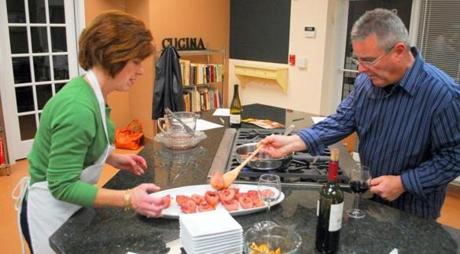 Valerie Riley helped her husband, Kevin Riley, make red wine-poached pears for dessert.