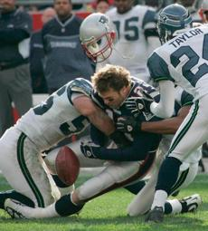 Tom Brady's helmet popped off and he fumbled on this crunch by Seattle's Bobby Taylor, right, and Chike Okeafor.
