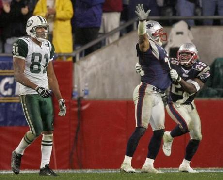 Eugene Wilson, right, celebrated with Rodney Harrison after breaking up a pass play intended for the Jets' Justin McCareins with 2:08 remaining.