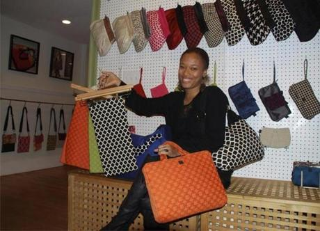 Studio Boston store manager Tania Shabazz displaying fabric and bag styles.