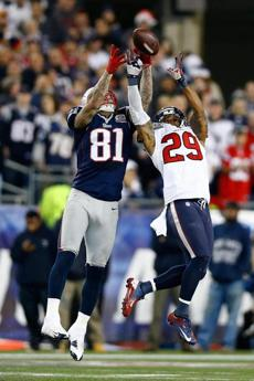 Tight end Aaron Hernandez (#81) of the New England Patriots and safety Glover Quin of the Houston Texans go up for the ball in the first half.