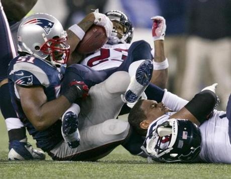 Jerod Mayo stopped the Texans' Arian Foster for no gain as his teammate Rya Harris lost his helmet during second half.