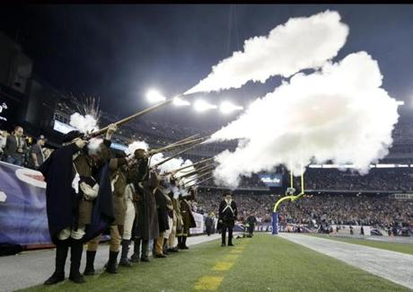 New England Patriots Minutemen actors fire rifles during the first quarter.
