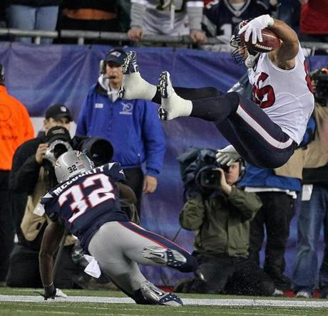 12/10/12: Foxborough, MA: THIRD QUARTER.........Texans fullback James Casey (86) is flipped by the Patriots Devin McCourty (32), but not before he picked up a 30 yard gain on a pass from quarterback Matt Schaub (not pictured) that gave Houston a first and goal at the New England two yard line and set up the first Texans touchdown of the game. The New England Patriots hosted the Houston Texans in an NFL Monday Night Football game at Gillette Stadium. section: sports topic: Texans-Patriots (Jim Davis/Globe Staff)
