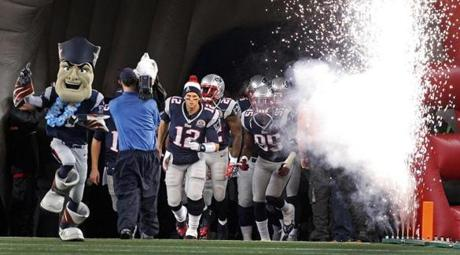 Patriots quarterback Tom Brady lead his team out for the start of the game accompanied by fireworks.