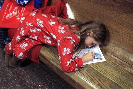 "Raquel Booth, 8, of Danvers was dressed in her pajamas as she wrote out her Christmas wish list while waiting to board the Polar Express in South Station. The commuter rail company hosted 25 local youth charities on a magical train ride to the ""North Pole."""